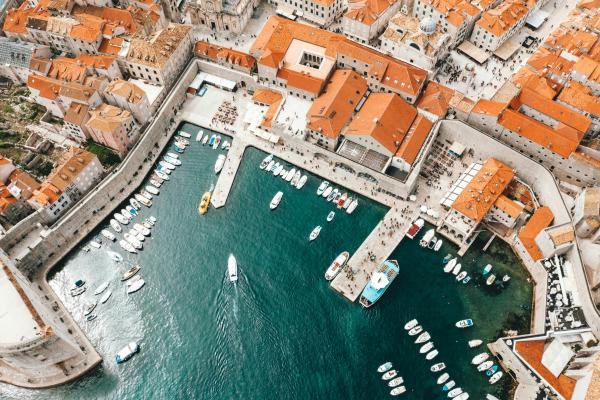 Dubrovnik - aerial photography of boats on pier and city